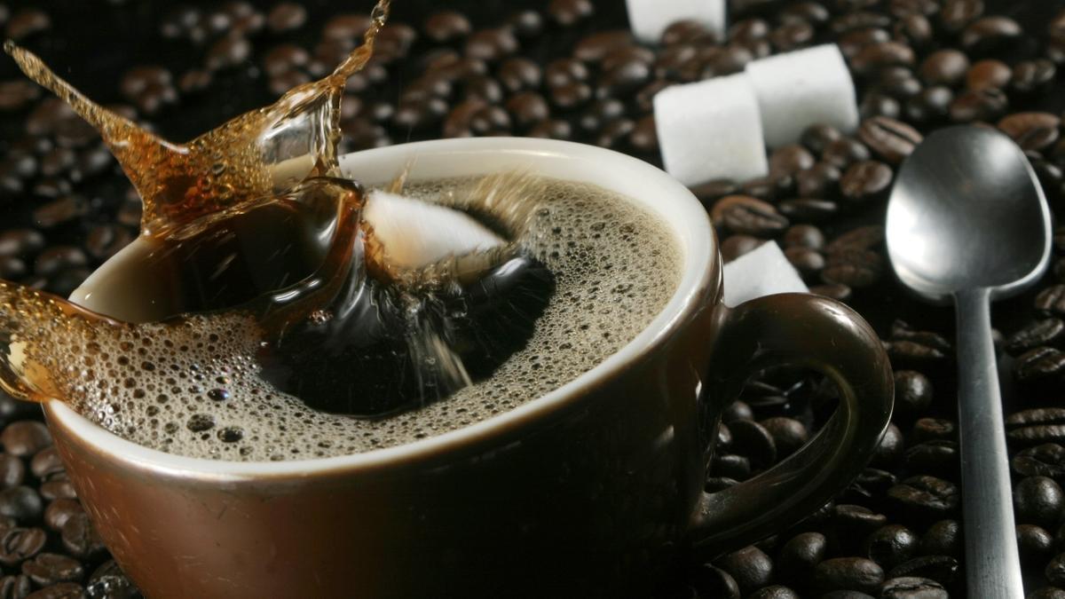 Tasse Kaffee, Kaffeebohnen und Zuckerwürfel