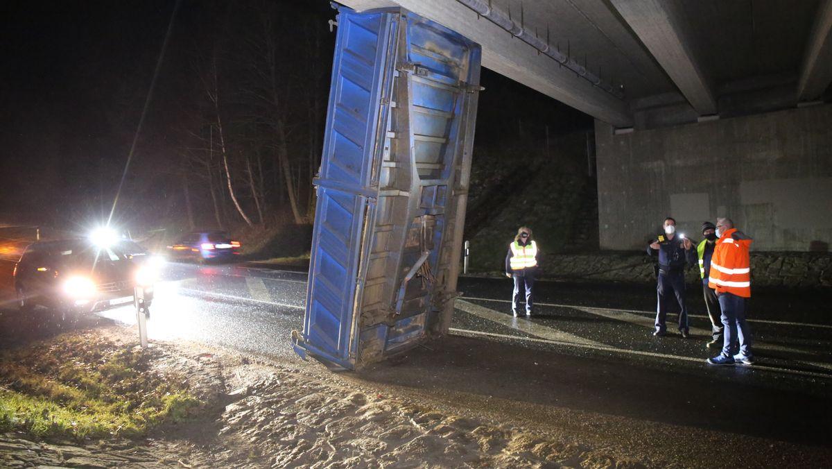 Die Mulde eines Lastwagens hat sich zwischen einer Brücke und der Straße verkeilt.