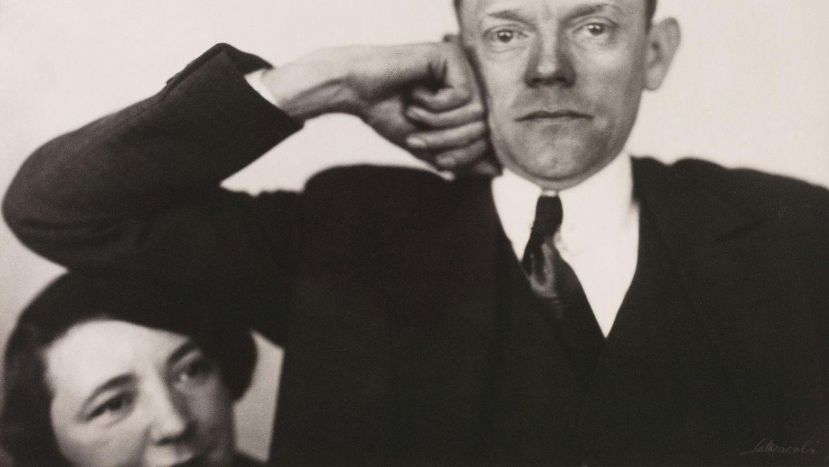 Ein Mann im schwarzen fährt seinen Arm zur Seite und drängt damit die Frau in den Hintergrund.