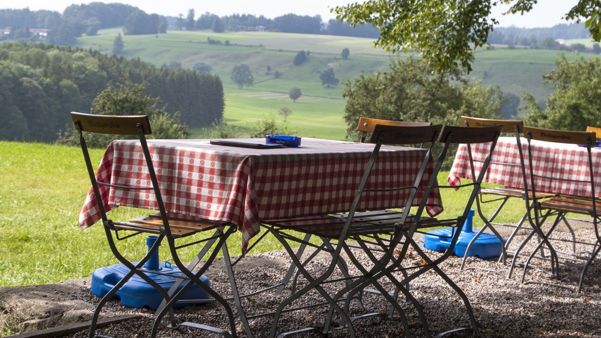 Leere Gartentische und Stühle stehen in einem Wirtsgarten.