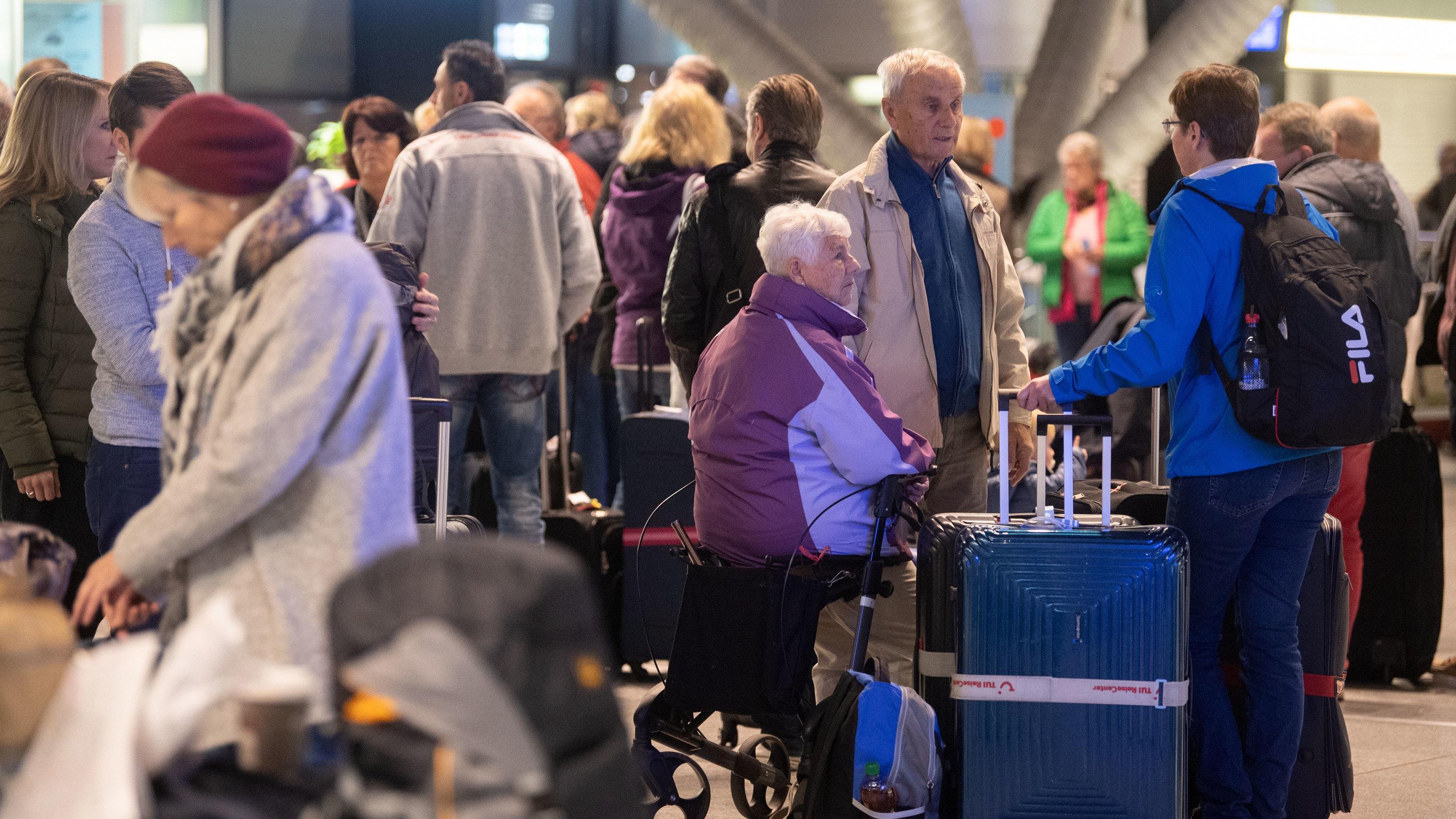 Vom Streik betroffene Passagiere warten am Flughafen Stuttgart