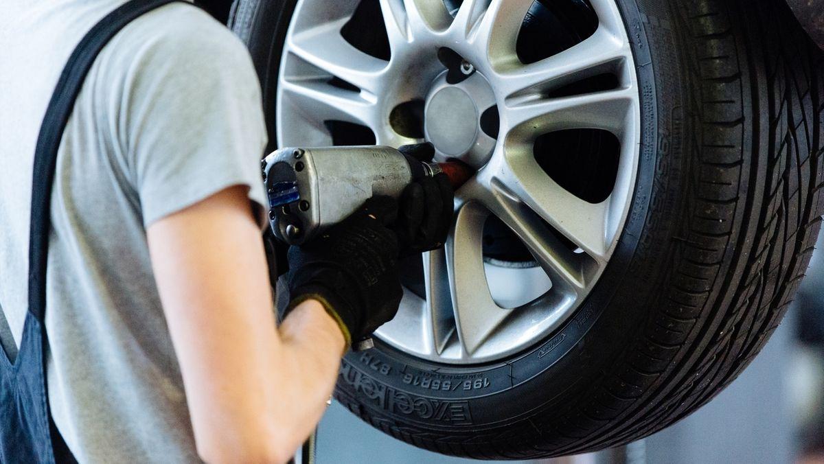 Monteur befestigt eine Reifen am Auto.