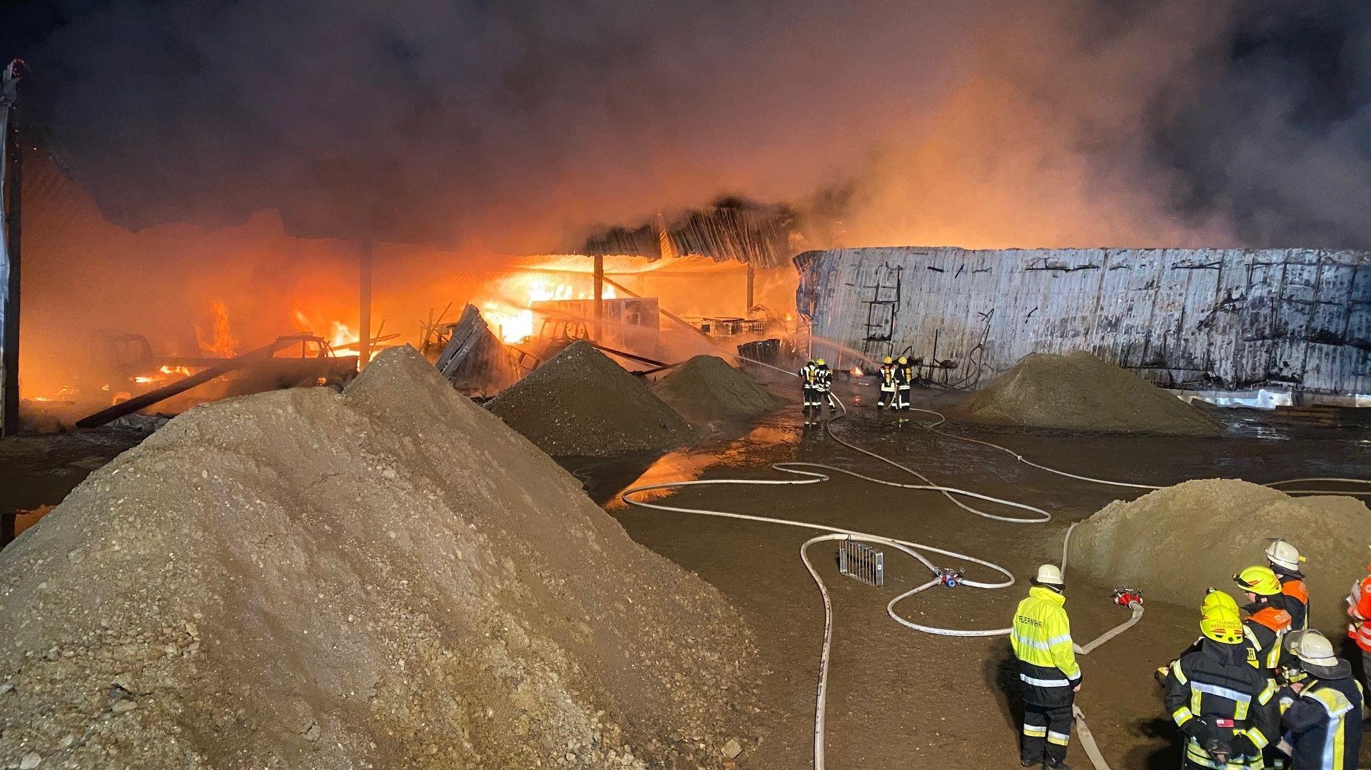 Bild vom Einsatzort - dichter Rauch über der brennenden Lagerhalle