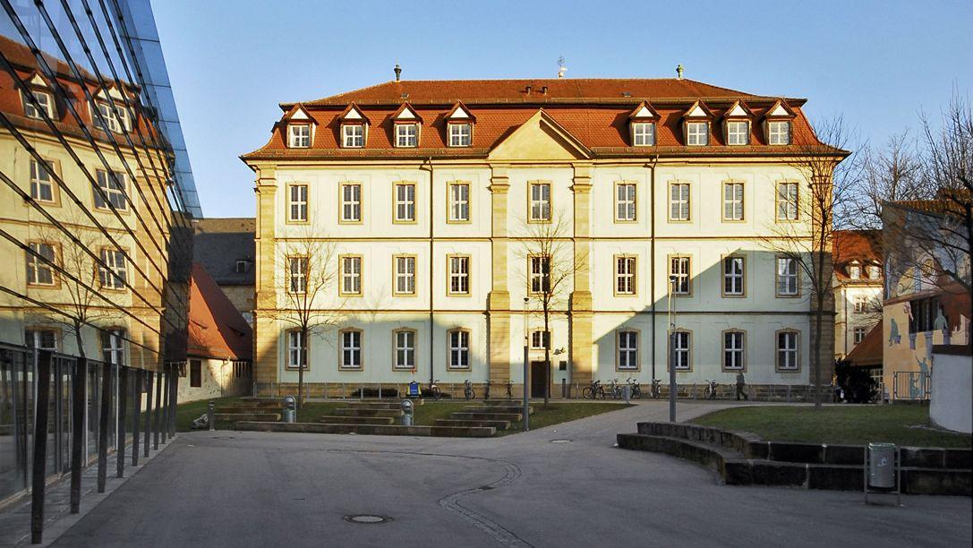 Die Fassade des Uni-Gebäudes in Bamberg, davor ein geteerter Platz.