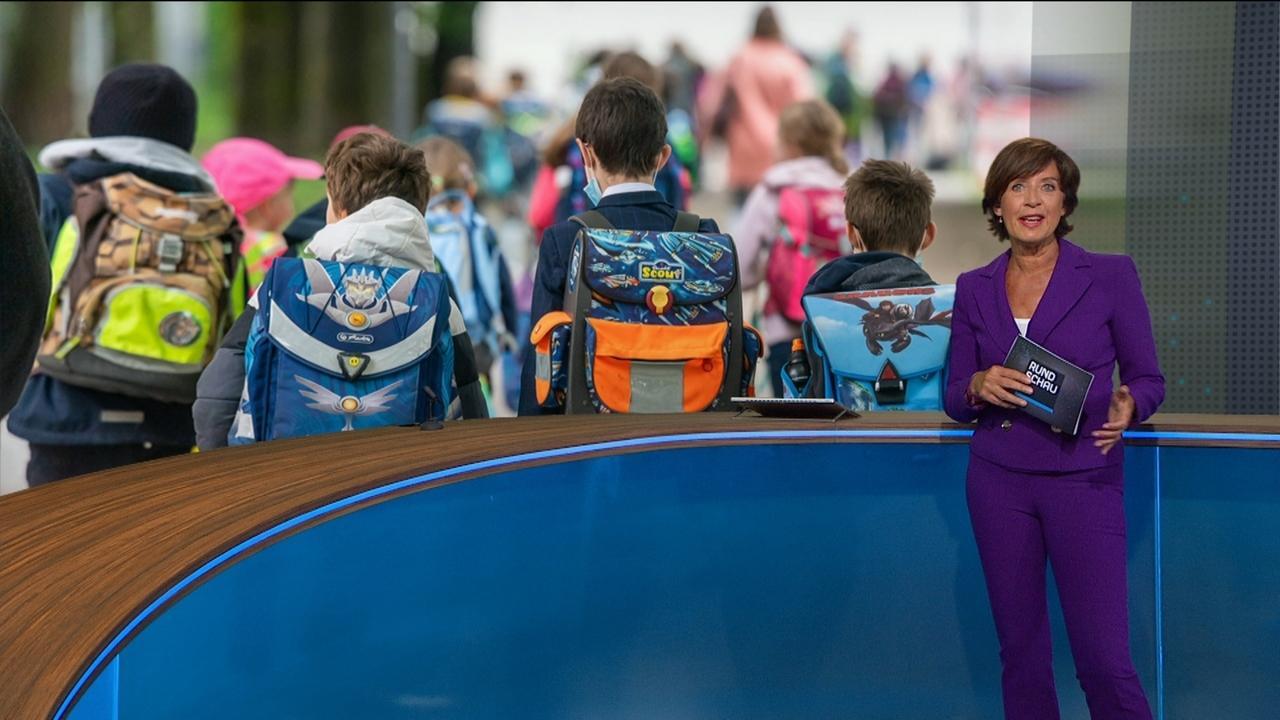 Ursula Heller vor Bild mit Kindern mit Schulränzen