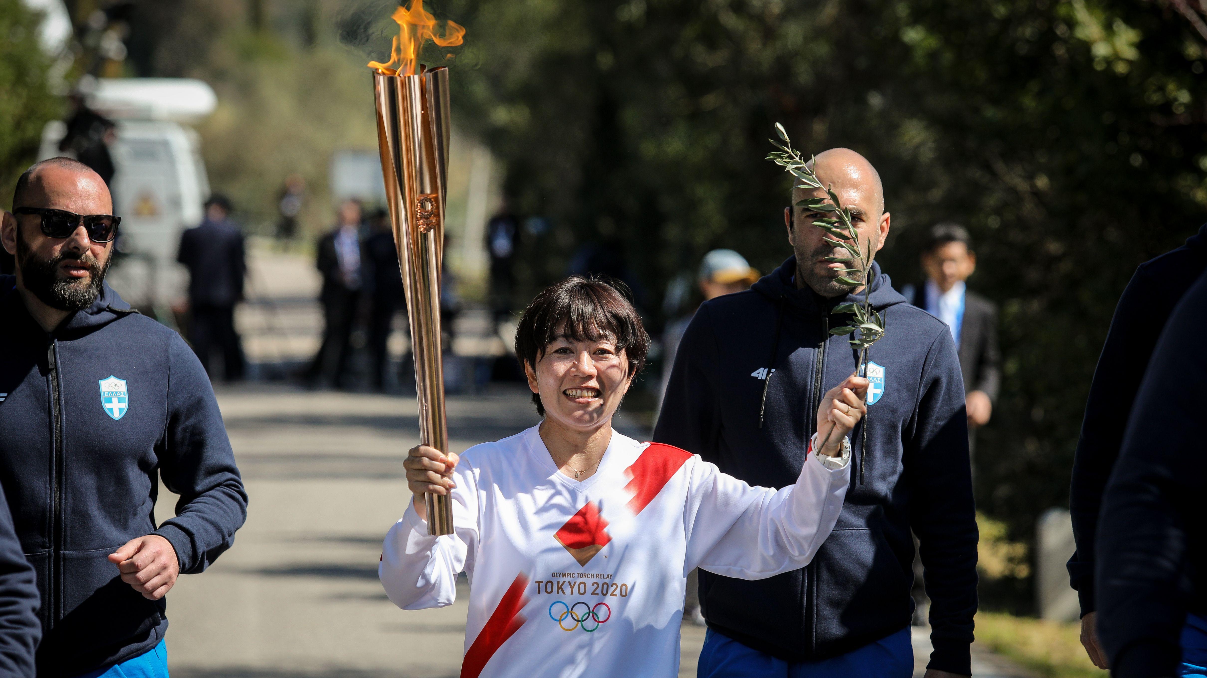 Läuferin nach der Entzündung des olympischen Feuers in Olympia