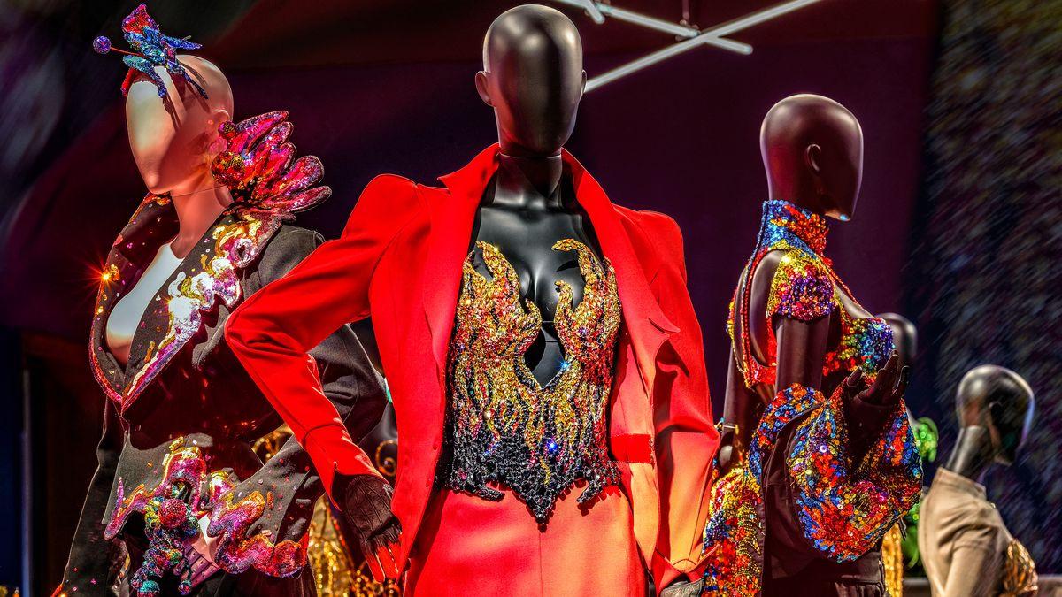 Ausstellungsansicht im Musée des beaux-arts de Montréal. Schaufensterpuppe mit leuchtend rotem Kostüm und bunt glitzerndem Korsett, das in Form von Flammen ausgeschnitten ist. Daneben zwei weitere Puppen mit bunten Glitzerkostümen.
