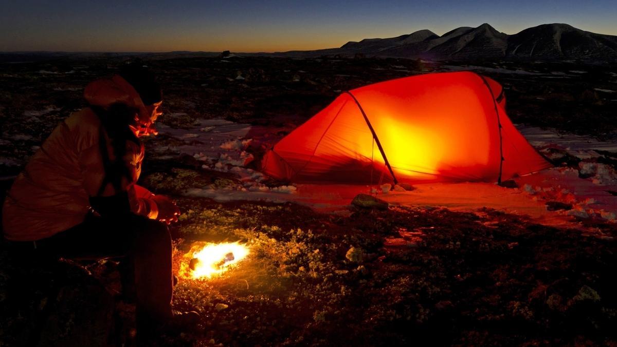 Mann am Lagerfeuer vor einem See