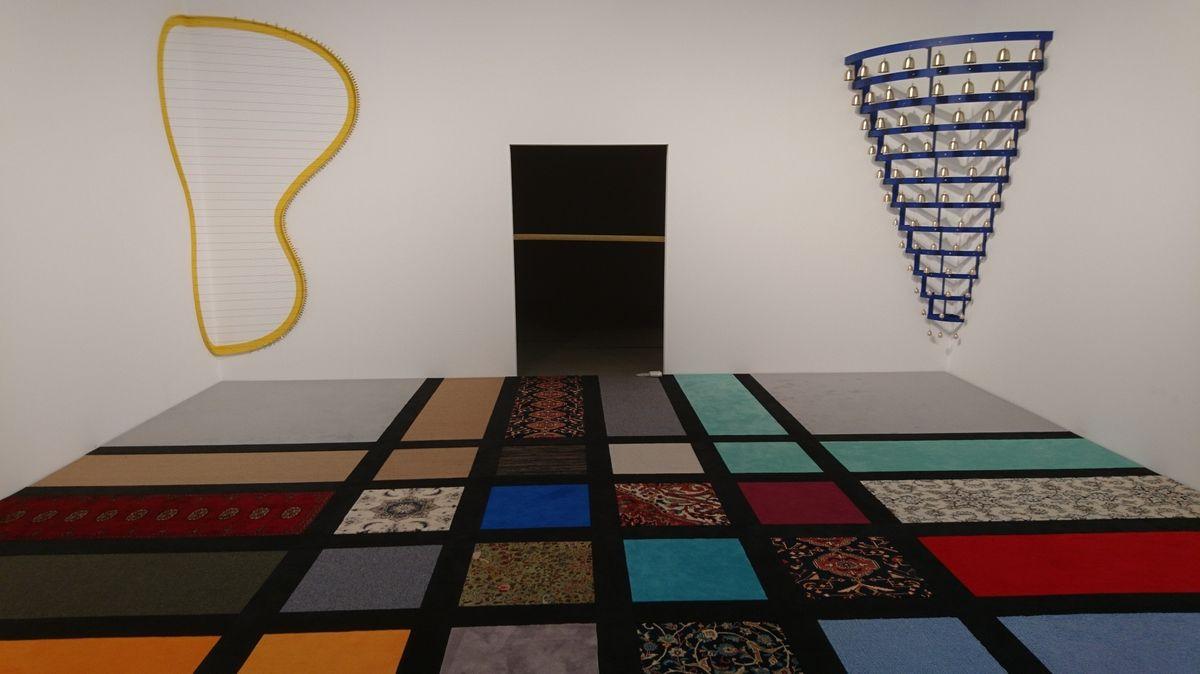 Verschiedenfarbige Teppiche mit verschiedenen Mustern lieben auf dem Fußboden eines Raums. Instrumentenartige Objekte stehen in den Ecken.