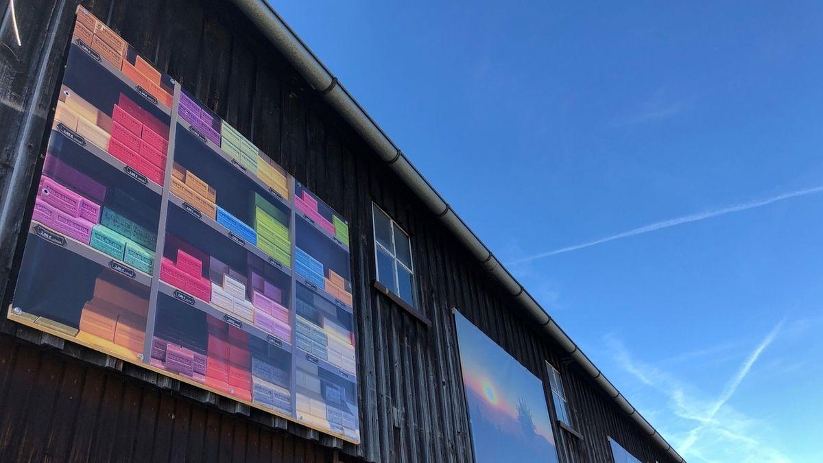 Plakate mit Abbildungen von bunten Seifen und Landschaftsaufnahmen hängen an der Stodlwand.