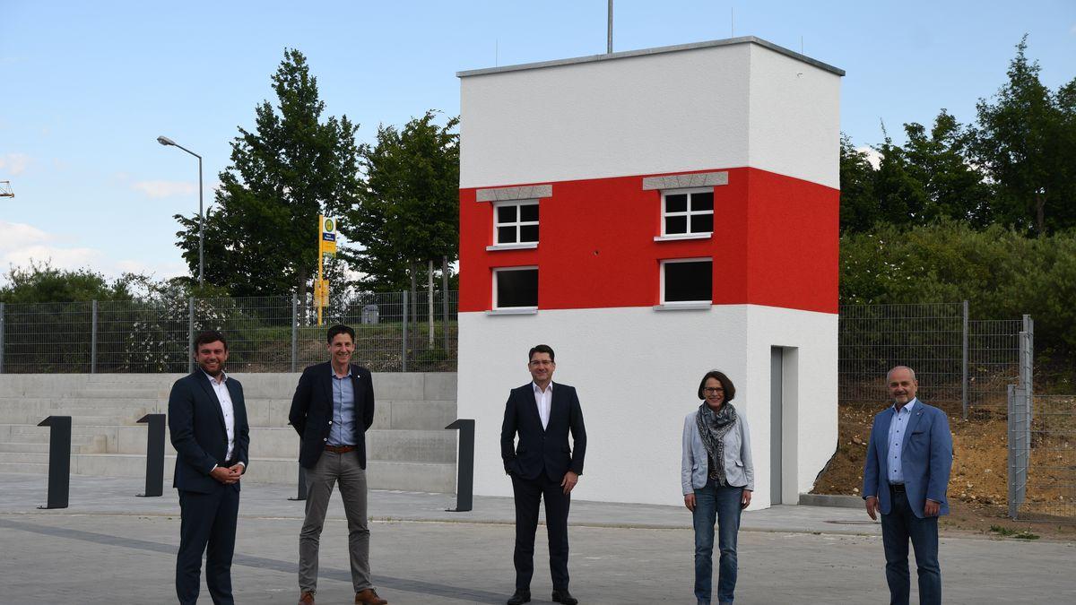 Fünf Menschen stehen vor einem rot-weißen Turm.