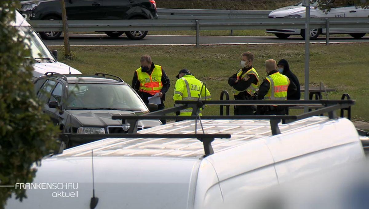 Mitarbeiter von Zoll und Polizei tragen gelbe Warnwesten und stehen hinter Einsatzfahrzeugen.