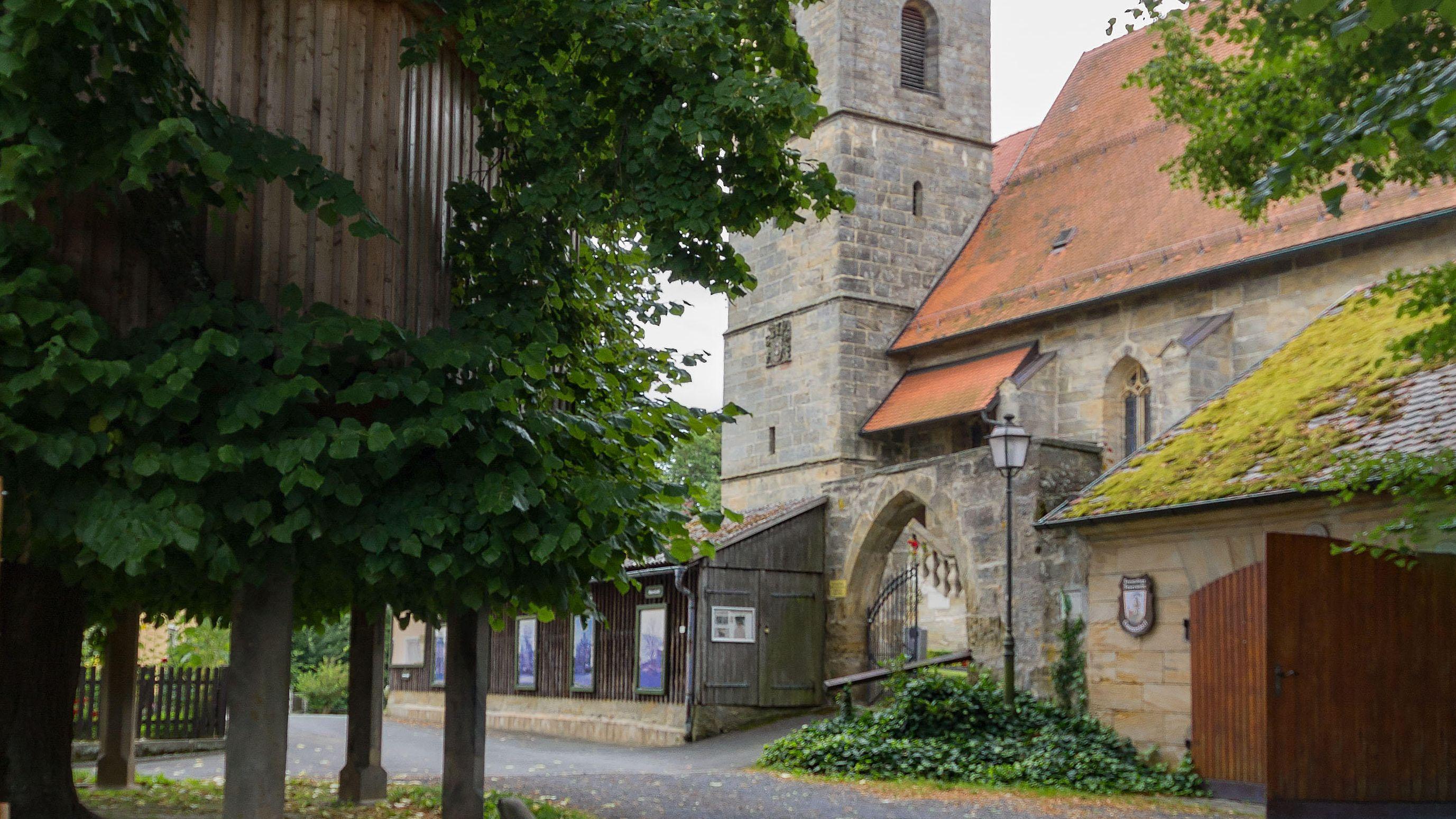Die Limmersdorfer Tanzlinde mit, zur Kirchweih, angebauter Treppe steht neben der Dorfkirche.