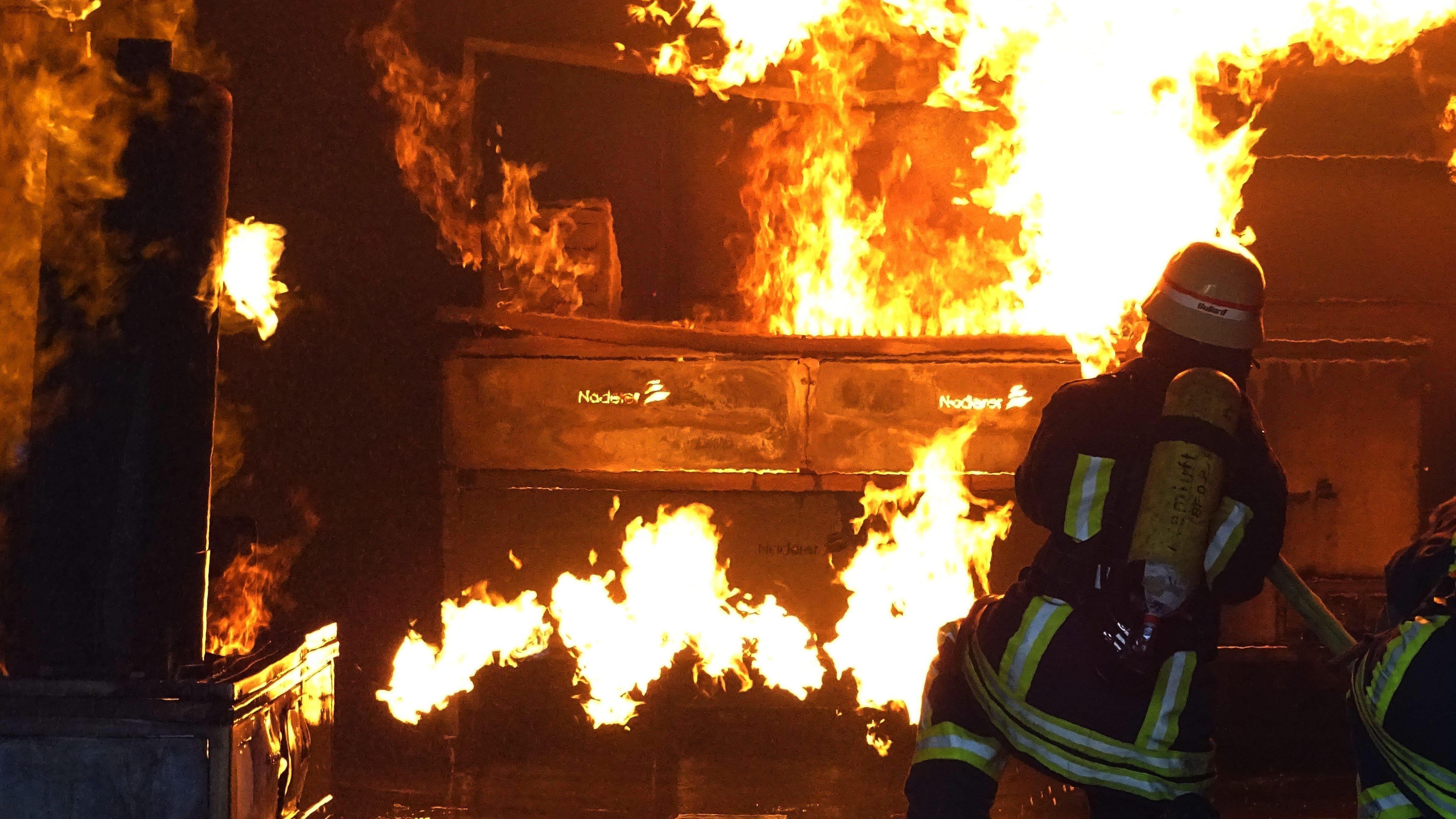 Feuerwehrmänner führen eine Realbrandlöschübung in einer Feuerwehrschule durch.