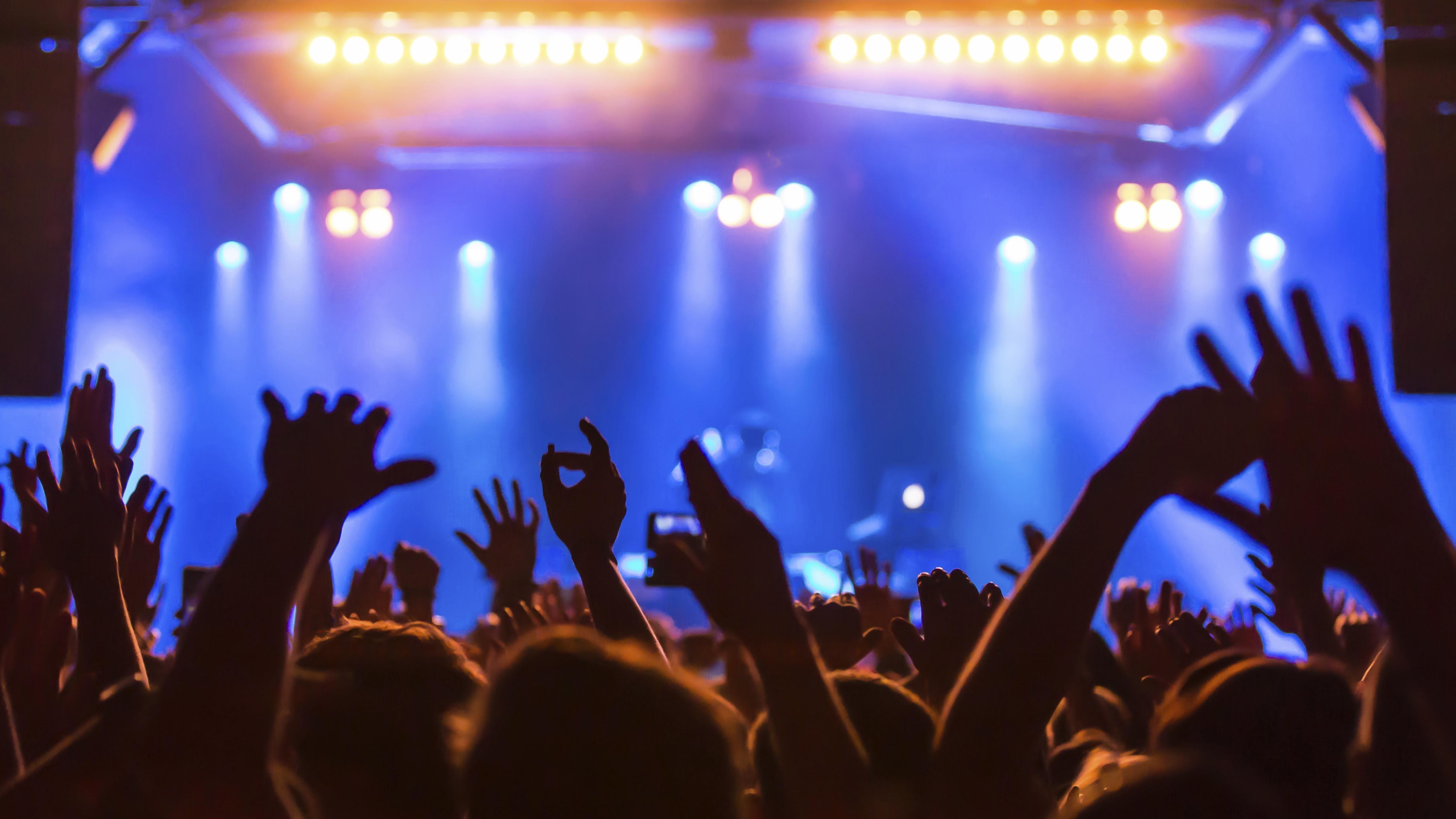 Besucher eines Konzertes halten Hände in die Luft.