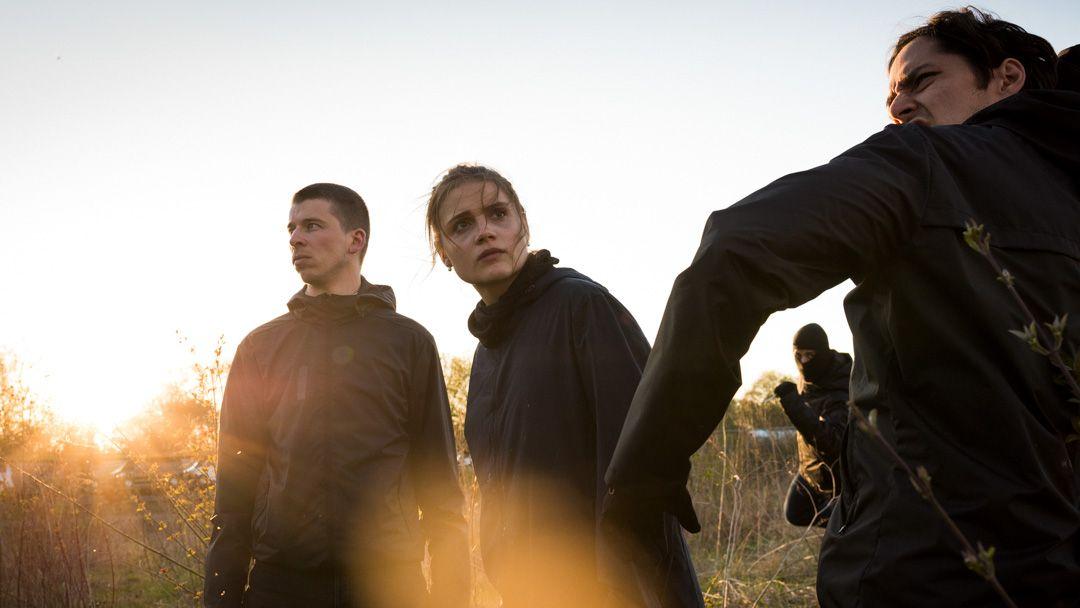 Zwei Männer und eine Frau stehen in der freien Natur und blicken ernst, im Hintergrund ein Mann mit schwarzer Gesichtsmaske.