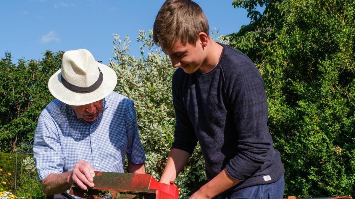 Ein Jugendlicher hilft einem Senioren bei der Gartenarbeit.