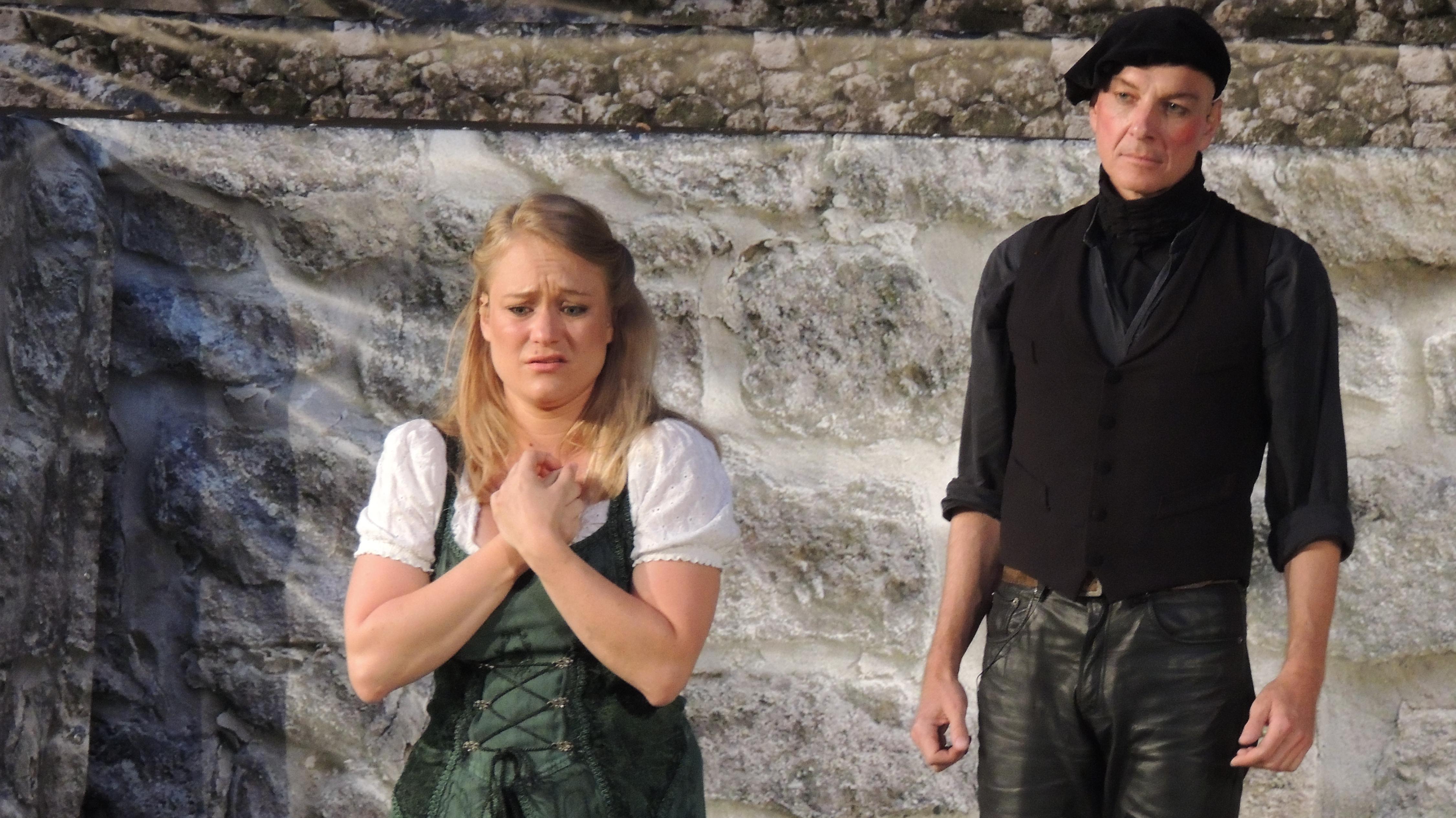 Szene der Faust-Festspiele: Eine blonde Frau hat die Hände vor der Brust gekreuzt, im Hintergrund steht ein Mann.