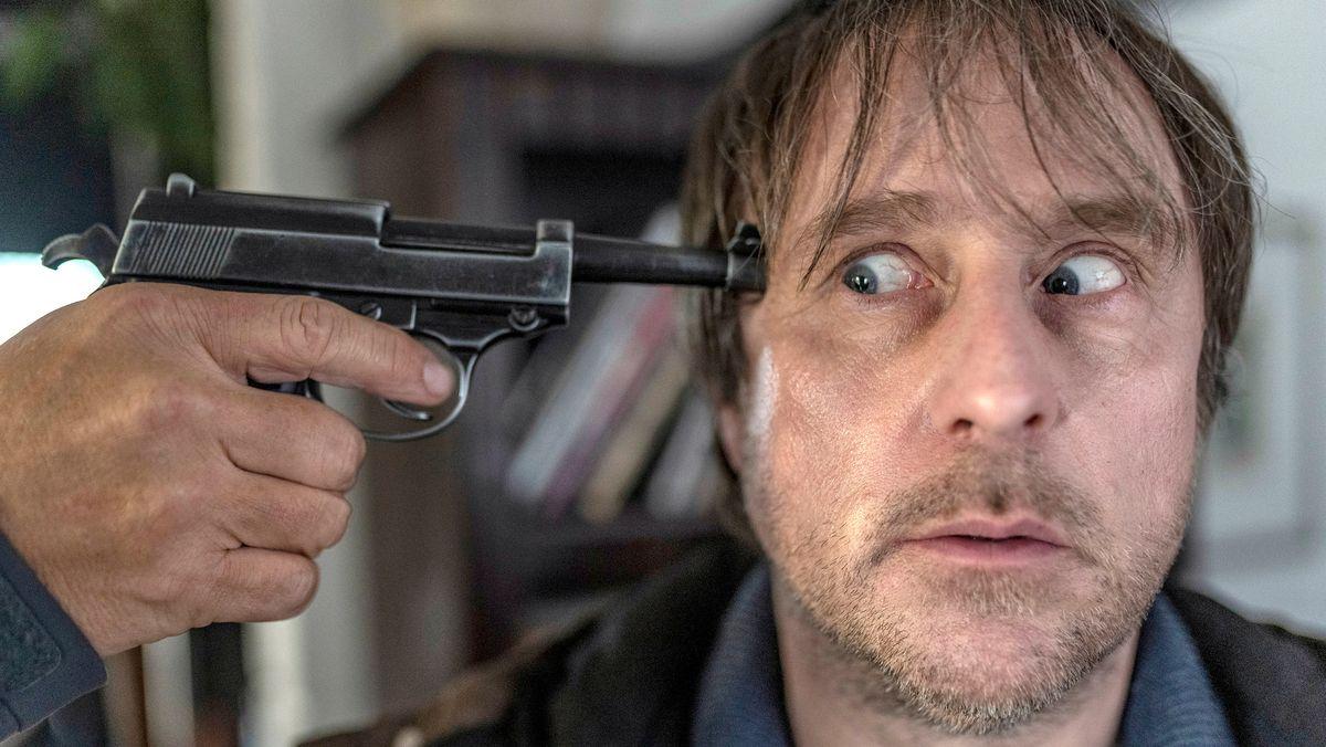 """Ausschnitt aus """"Sörensen hat Angst"""": Kriminalhauptkommissar Sörensen (Bjarne Mädel) mit Knarre am Kopf."""