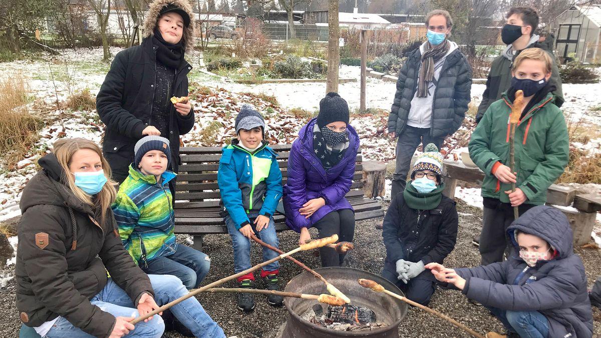 Kinder grillen Stockbrot über dem Feuer.