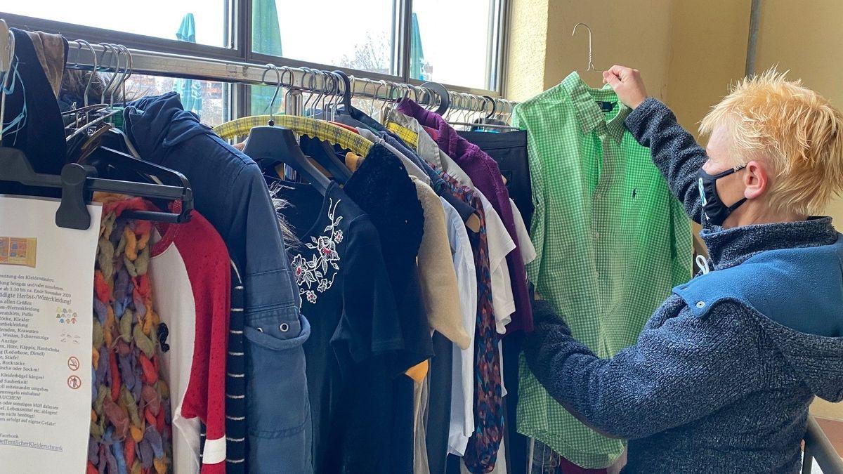 Eine Frau schaut beim öffentlichen Kleiderständer in Traunstein Klamotten durch.