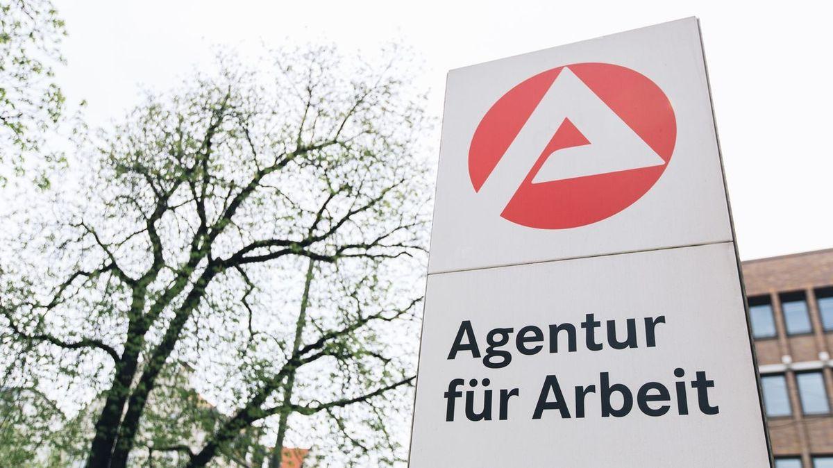 """Rot-weißes Schild mit schwarzer Aufschrift """"Agentur für Arbeit""""."""