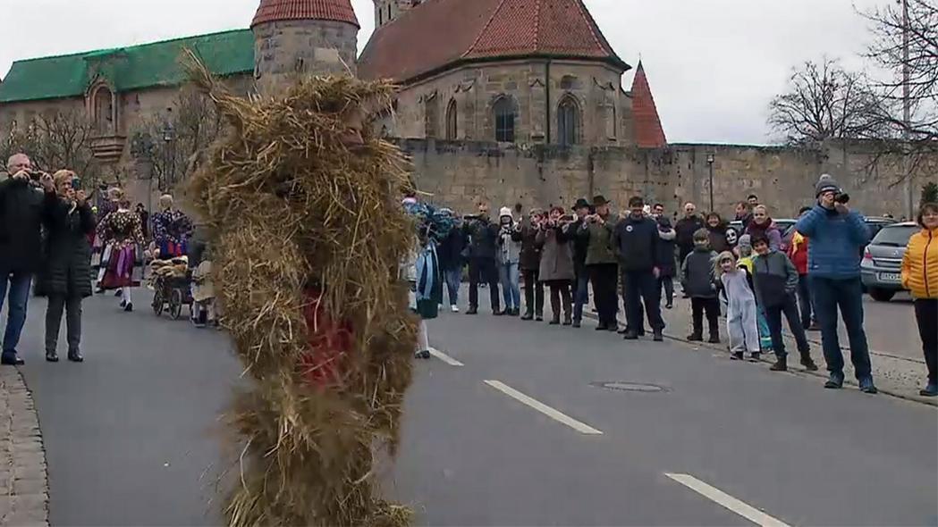 Ein Mann in einem Strohkostüm läuft durch Baiersdorf.