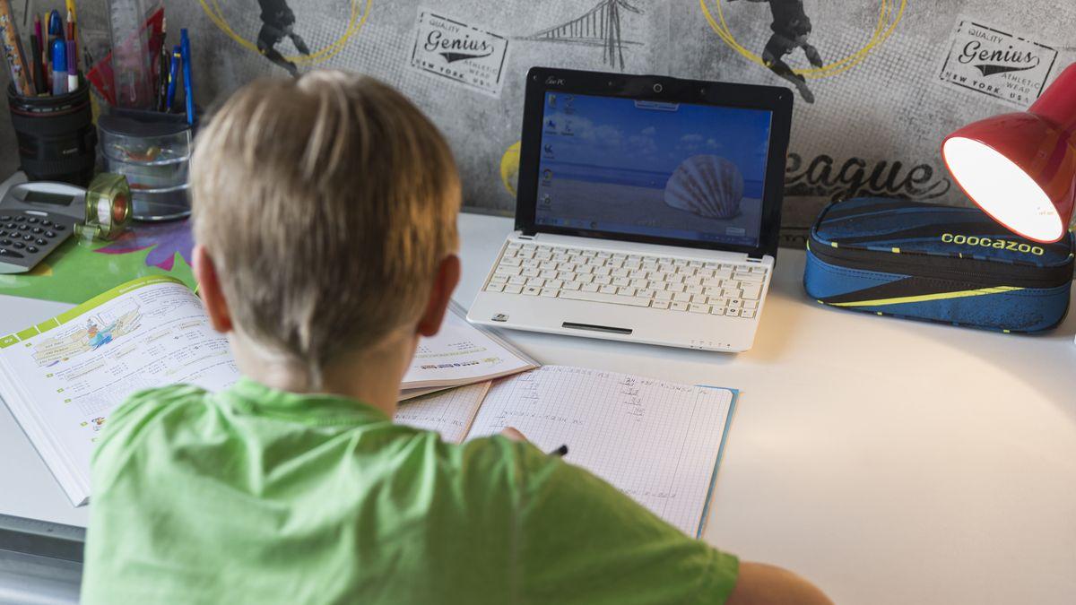 Ein junge sitzt an seinem Schreibtisch und erledigt seine Mathe-Aufgaben im Homeschooling.