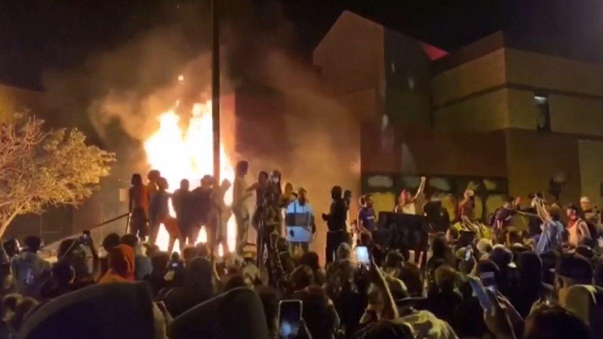 Menschenmenge bei Nacht, im Hintergrund stehen Menschen auf einer Treppe oder Balustrade, hinter ihnen brennt ein Feuer, Flammen schlagen in die Hhöhe.