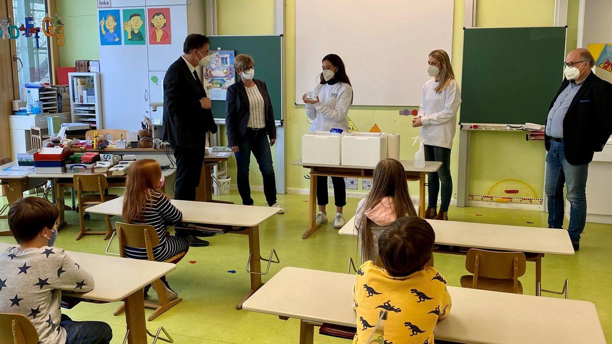 Schüler schauen in Richtung Lehrerpult, wo eine Frau den Gurgel-Test erklärt.