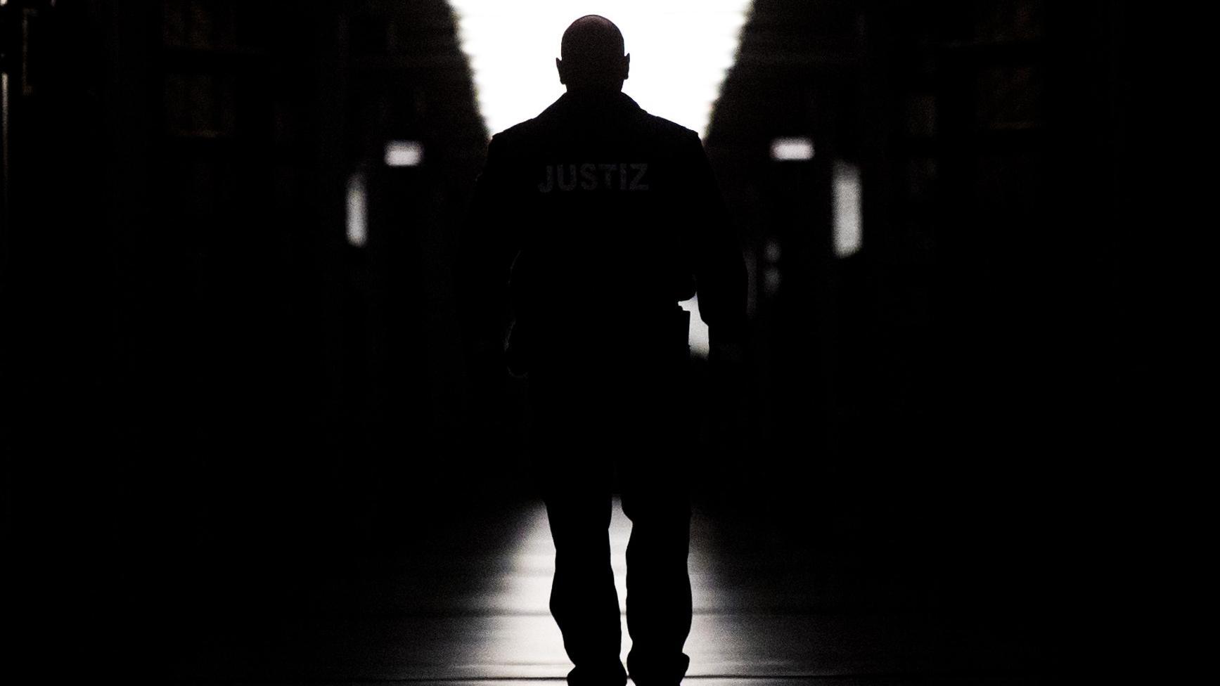 Ein Polizist geht in einem Gefängnis einen langen dunklen Gang entlang (Symbolbild)