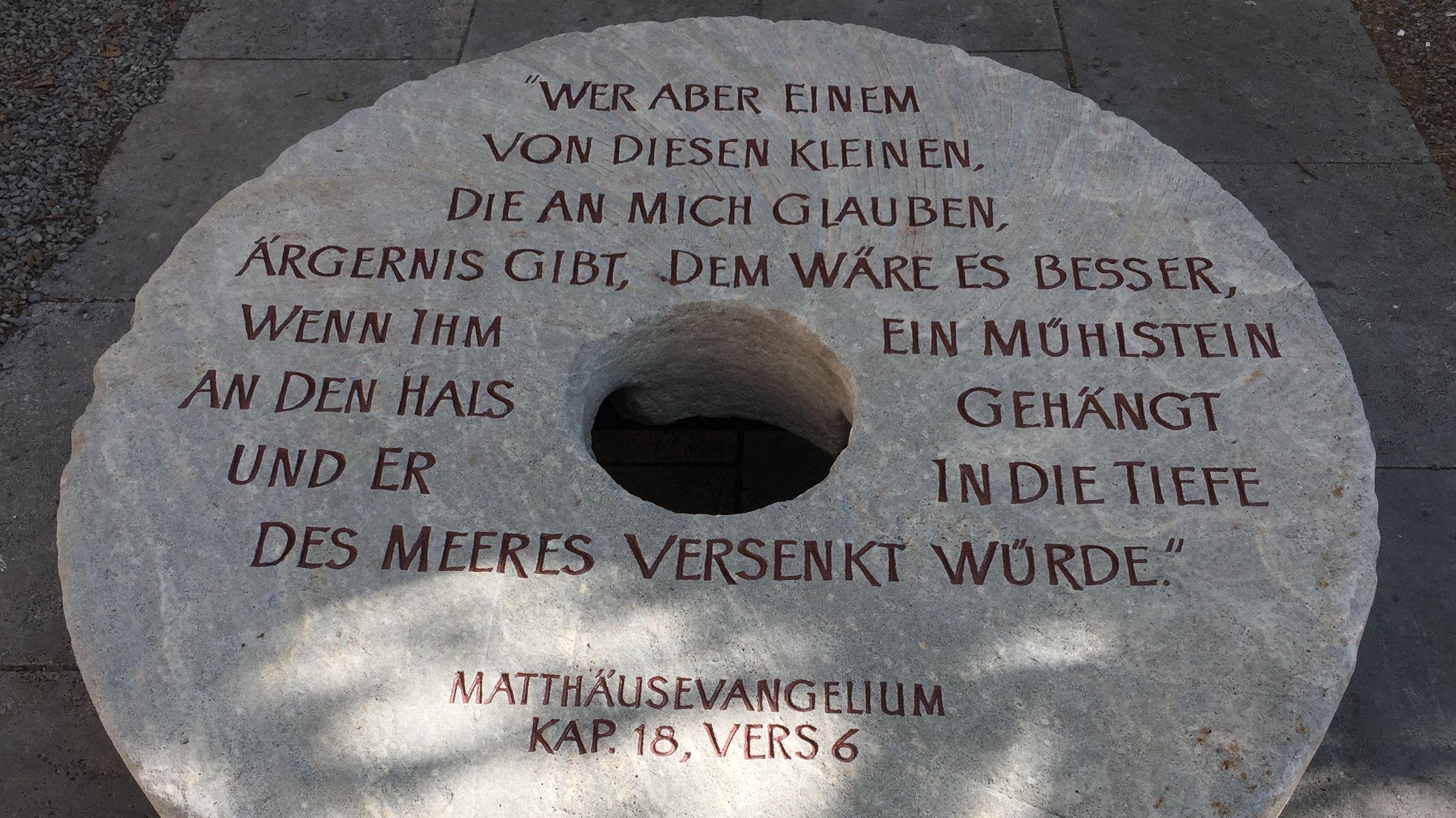 """Mühlstein hinter dem Dom, mit eingemeißelter Inschrift: """"Wer aber einem von diesen Kleinen, die an mich glauben, Ärgernis gibt, dem wäre es besser, wenn ihm ein Mühlstein an den Hals gehängt und er in die Tiefe des Meeres versenkt würde."""""""