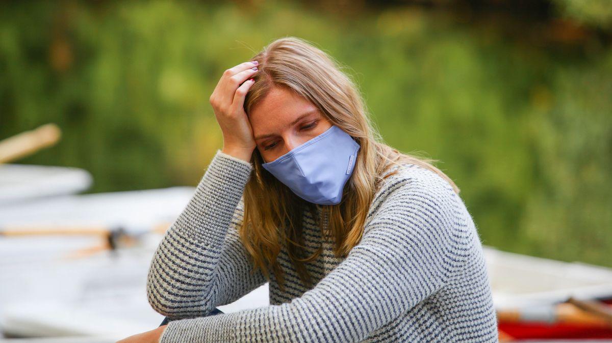 Eine Frau mit Maske sitzt draußen, sie hat einen betrübten Gesichtsausdruck.