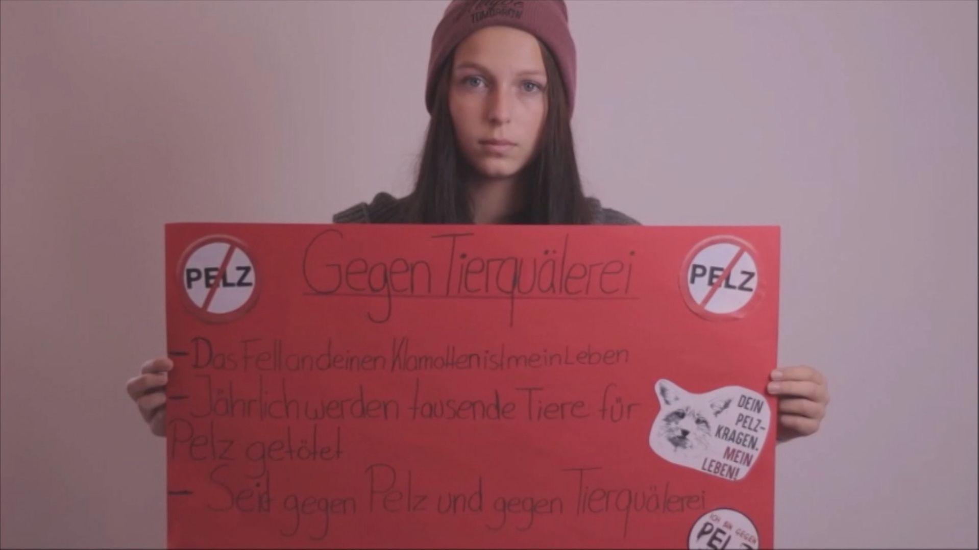 Schülerin mit Plakat gegen Tierquälerei