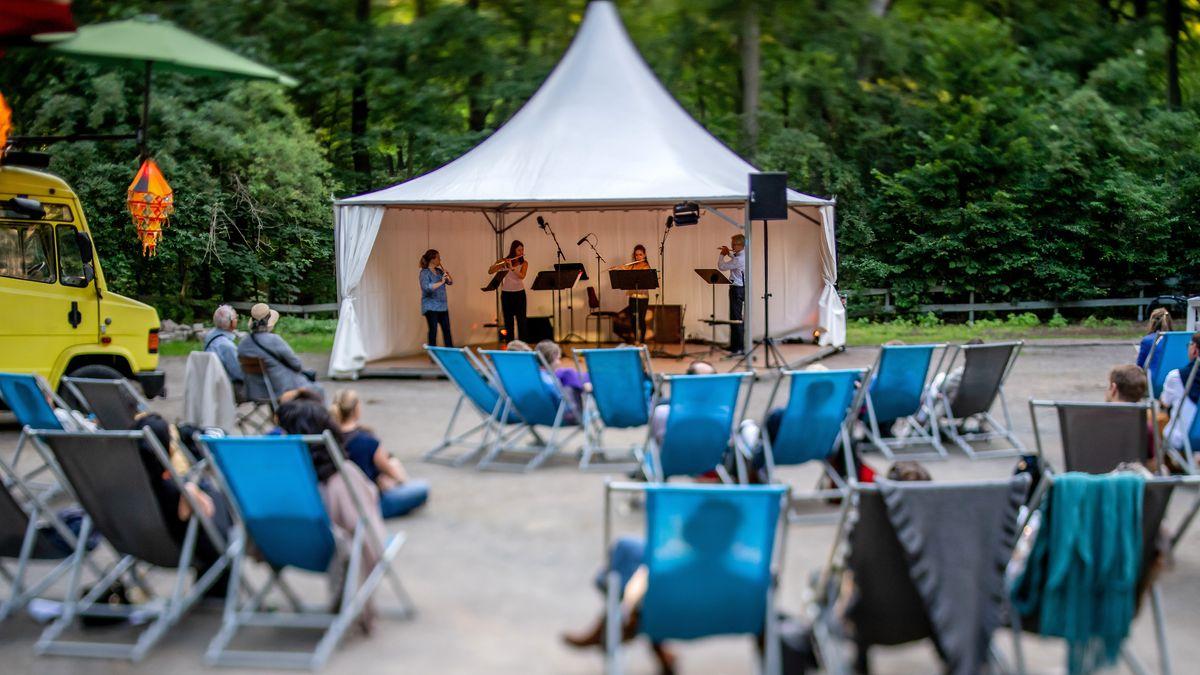 Zuschauer in Liegestühlen vor einem Zelt mit Musikern