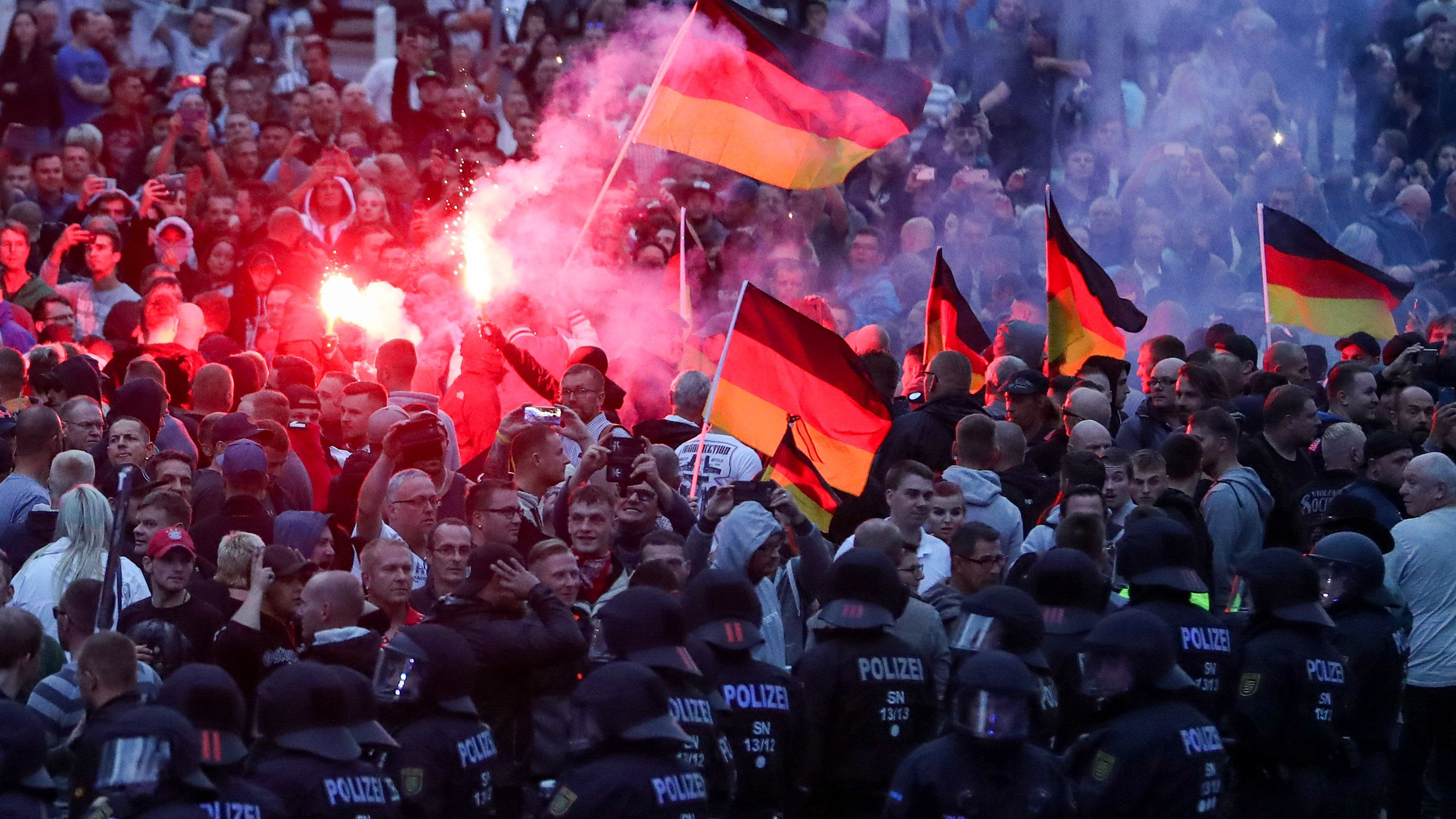 Demonstranten der rechten Szene zünden am 27.08.2018 in Chemnitz Pyrotechnik und schwenken Deutschlandfahnen.