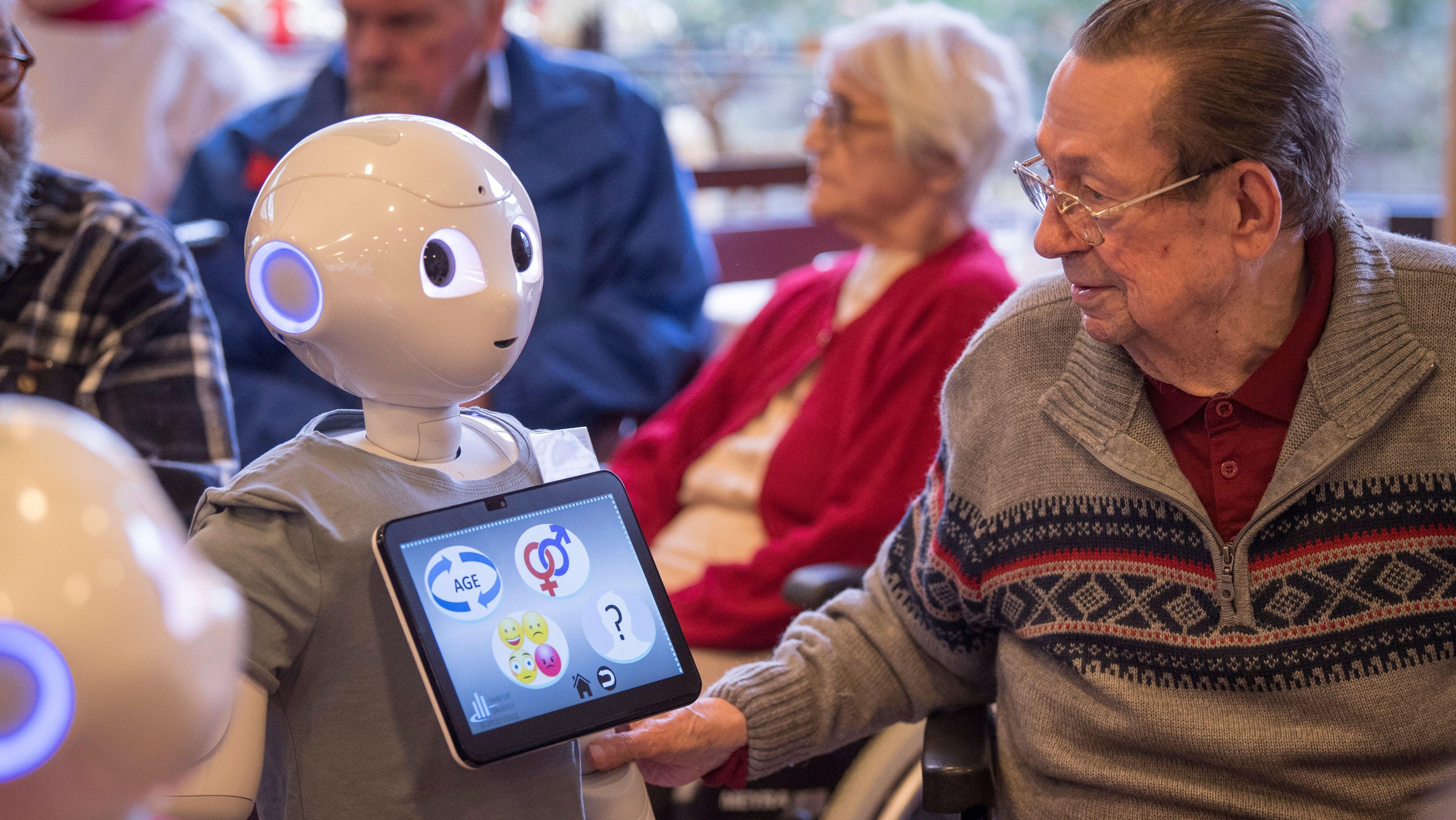 """Der humanoide Roboter """"Pepper"""" mit Bewohnern eines Alten- und Pflegeheims"""