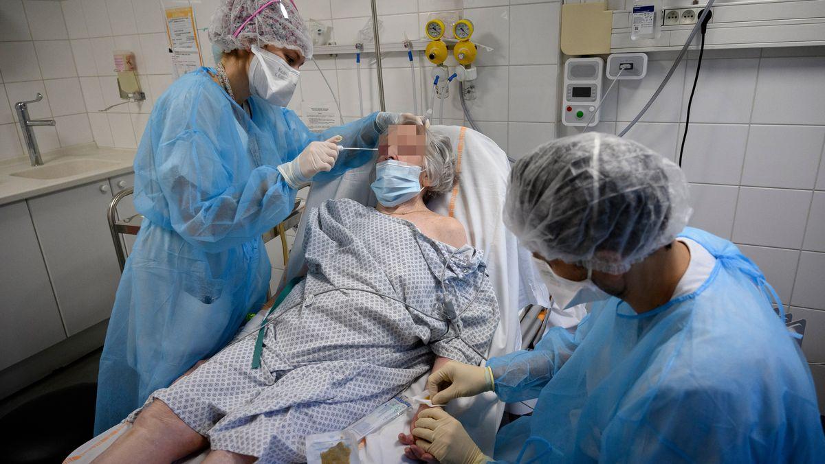 Krankenpfleger  kümmern sich auf der Intensivstation um eine Covid-Patientin