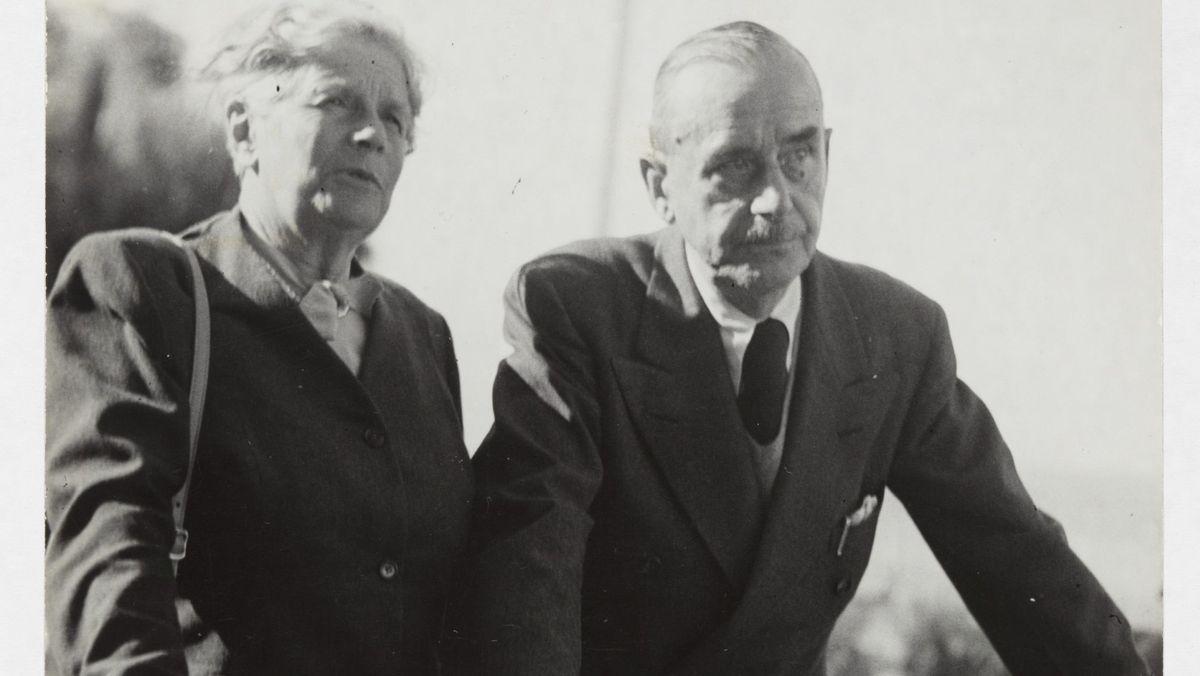 Thomas Mann und seine Frau Katia lehnen gemeinsam an einem Geländer und blicken in die Ferne. Schwarz-weiß Foto.
