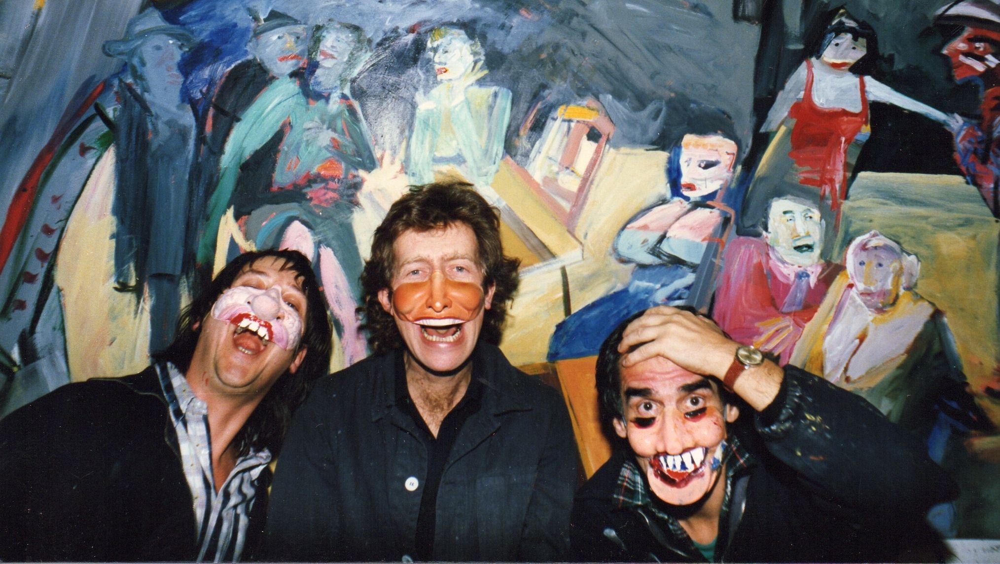 Die drei Gründer des King Kong Kunstkabinetts posieren mit Masken vor einem ihrer Werke (Aufnahme aus dem Jahr 1987)