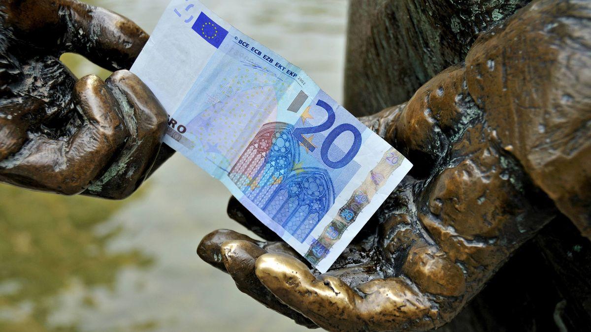 20-Euro-Schein zwischen den Händen einer Figur