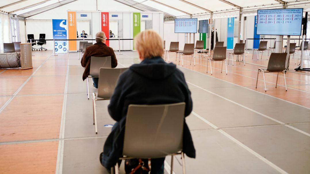 Mit Impfstoff von Biontech geimpfte Mitarbeiter sitzen im BASF-Impfzentrum im Wartebereich, in dem mögliche Nebenwirkungen der Corona-Impfung beobachtet werden.