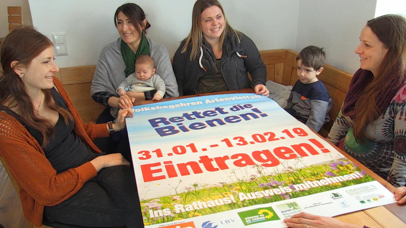 Familie am Tisch mit Plakat zum Volksbegehren.