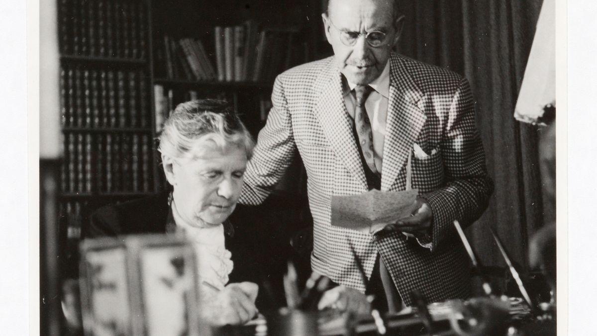 Schwarz-weiß-Foto zeigt Katia und Thomas Mann im Arbeitszimmer, Pacific Palisades, 1948. Sie sitzt am Schreibtisch, er steht hinter ihr, liest etwas vor, sie schreibt mit.