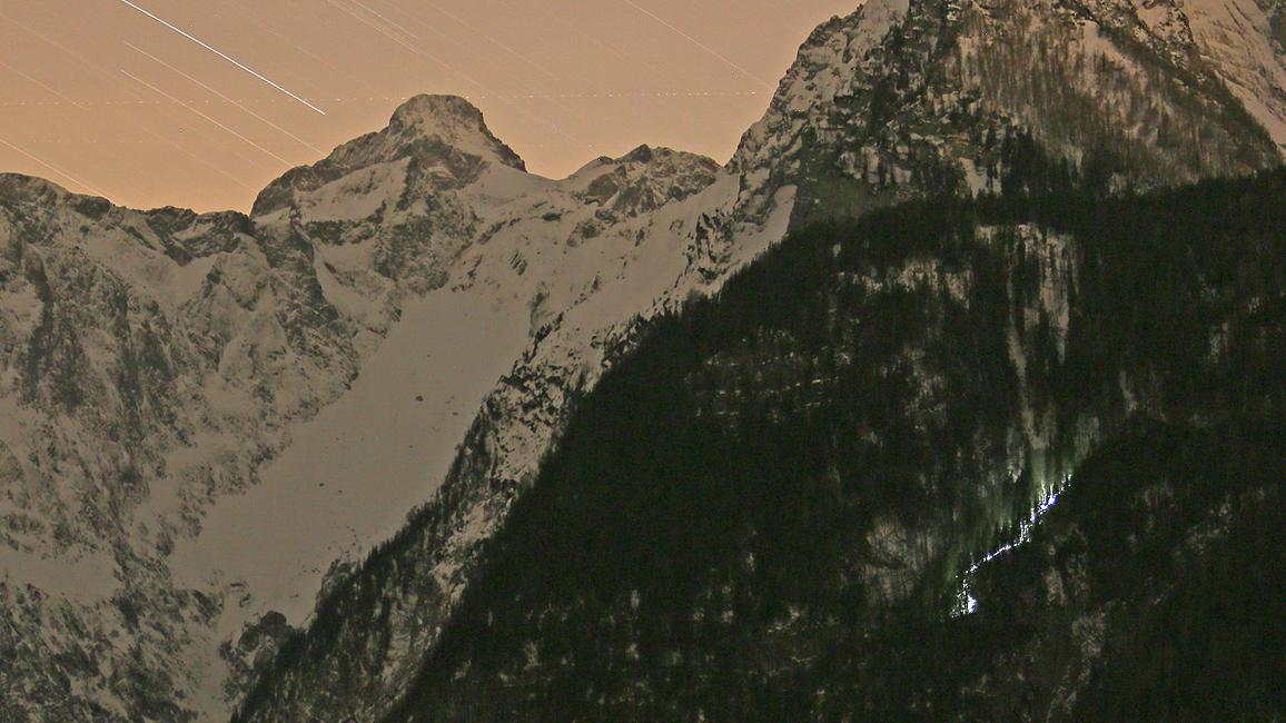 Die Echowand (bewaldet, rechts) am Königssee vor dem Watzmann-Massiv - gut sichtbar: das Helm-Licht der vielen Bergretter im Hang