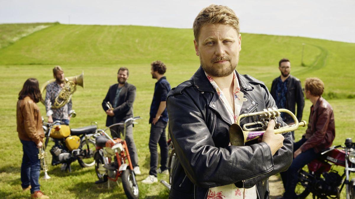 Stefan Dettl und LaBrassBanda-Kollegen mit Instrumenten und Mopeds auf einer Weide.