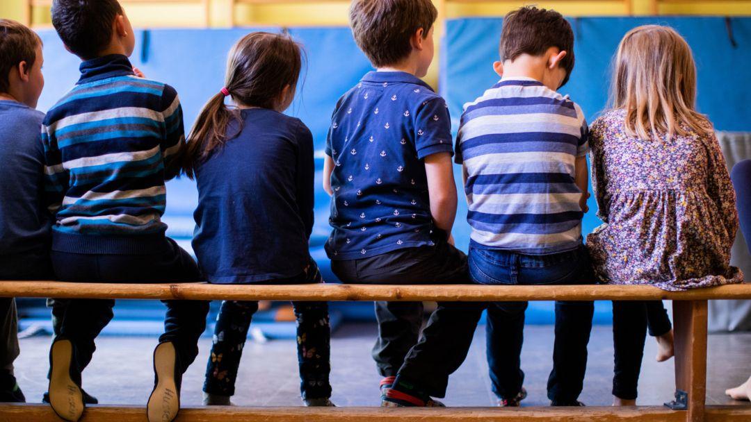 Kinder sitzen in einer Kindertagesstätte beim Sport auf einer Bank.