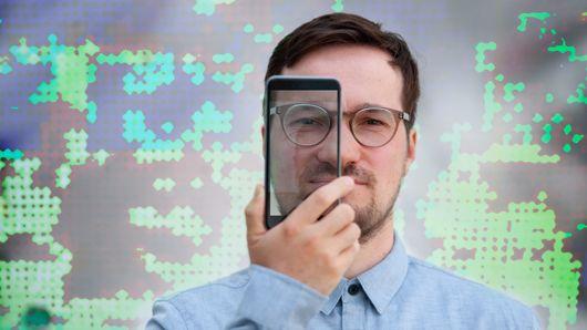 Clemens Stachl schaut durch eine gläserne Smartphone-Abdeckung.