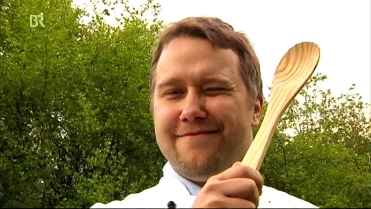 Ein Mann mit Kochlöffel in der Hand