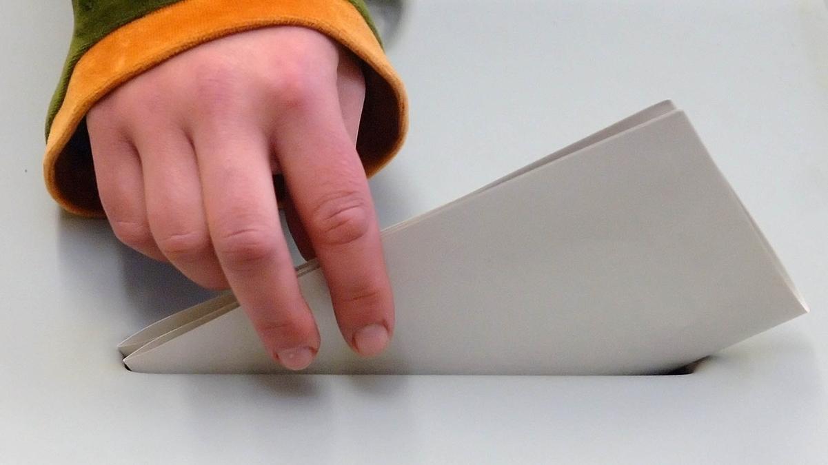 Eine Hand steckt einen Zettel in eine Wahlurne.